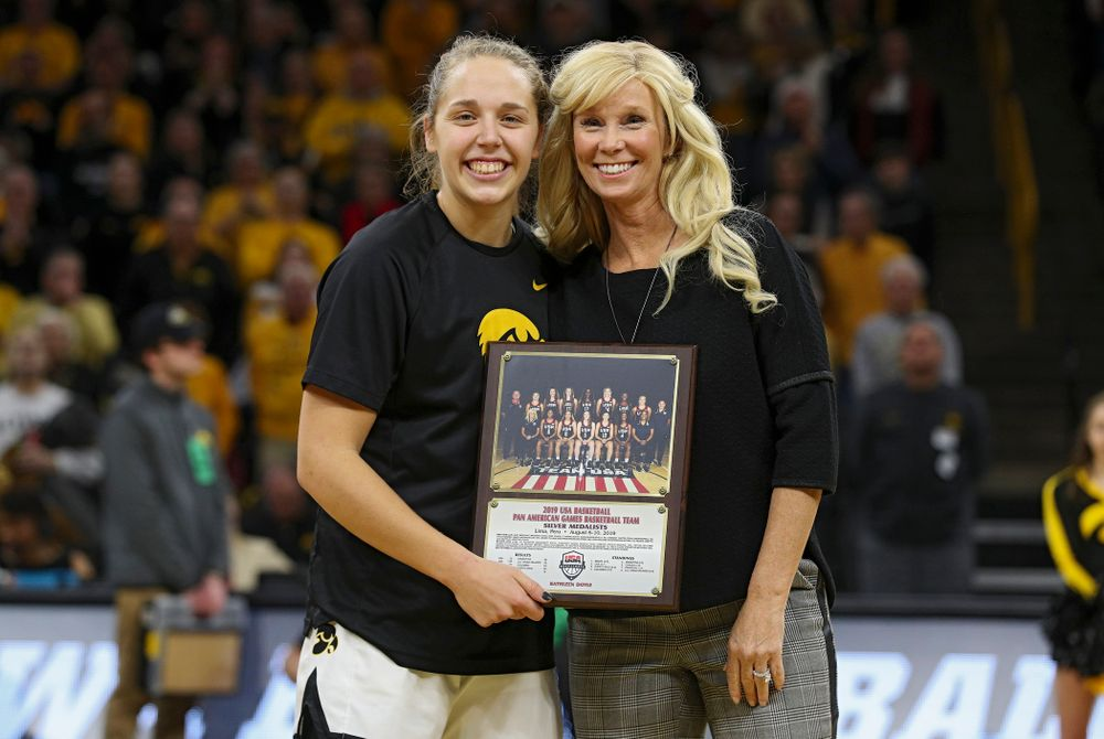 Iowa Hawkeyes guard Kathleen Doyle (22) is honored as a member of Team USA's 2019 Pan American Games team by the team's head coach Michigan State Spartans head coach Suzy Merchant before the start of their game at Carver-Hawkeye Arena in Iowa City on Sunday, January 26, 2020. (Stephen Mally/hawkeyesports.com)