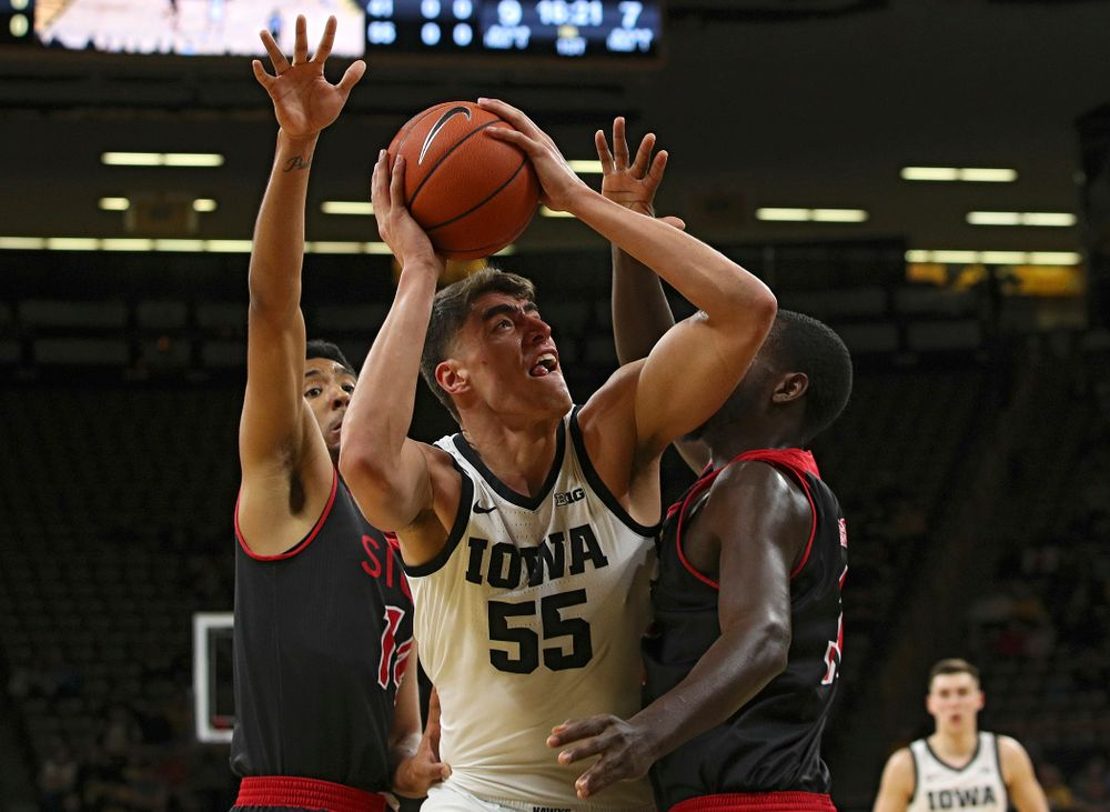 Iowa Hawkeyes center Luka Garza (55) shoots between two defenders during the first half of their game at Carver-Hawkeye Arena in Iowa City on Friday, Nov 8, 2019. (Stephen Mally/hawkeyesports.com)