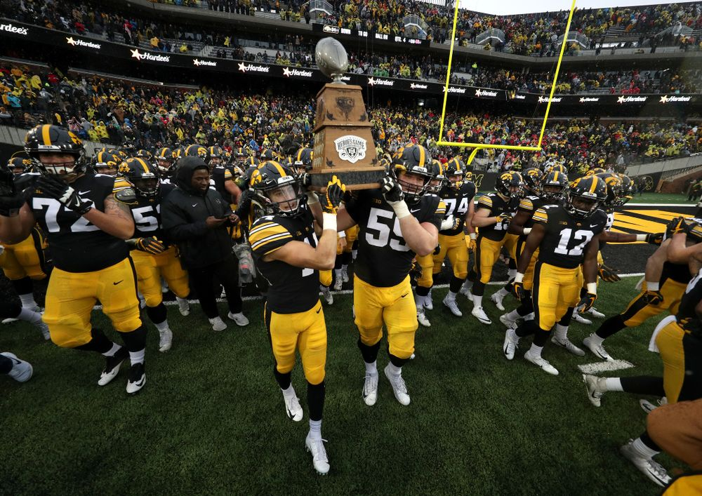 Iowa Hawkeyes wide receiver Kyle Groeneweg (14) and Iowa Hawkeyes offensive lineman Ross Reynolds (59) carry the Heros game trophy off the field following their win over the Nebraska Cornhuskers Friday, November 23, 2018 at Kinnick Stadium. (Brian Ray/hawkeyesports.com)