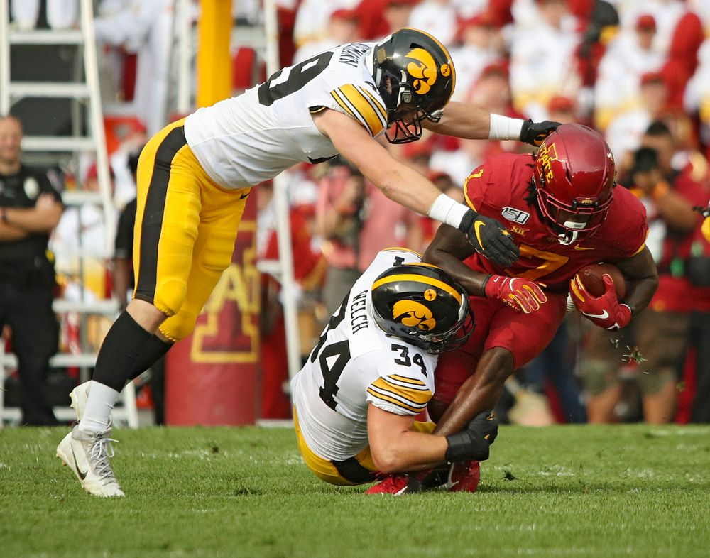 Iowa Hawkeyes linebacker Nick Niemann (49) and linebacker Kristian Welch (34) make a tackle during the first quarter of their Iowa Corn Cy-Hawk Series game at Jack Trice Stadium in Ames on Saturday, Sep 14, 2019. (Stephen Mally/hawkeyesports.com)