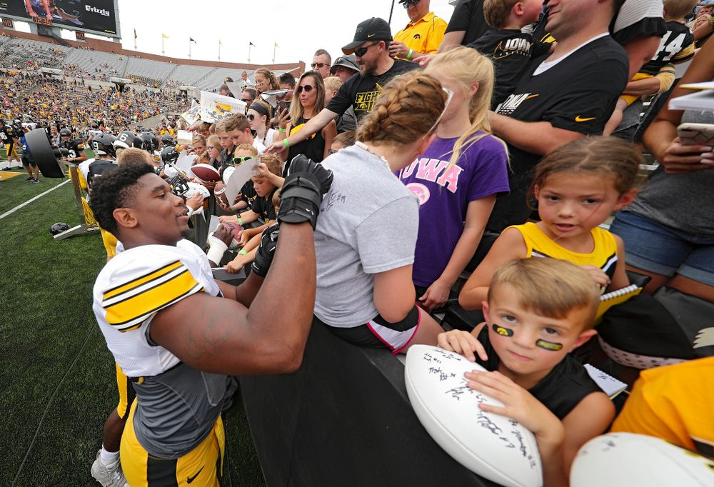 Iowa Hawkeyes defensive end Chauncey Golston (57) signs an autograph on a shirt during Kids Day at Kinnick Stadium in Iowa City on Saturday, Aug 10, 2019. (Stephen Mally/hawkeyesports.com)