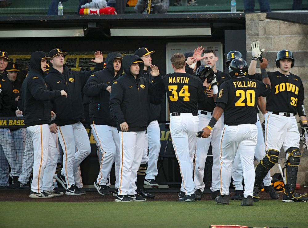 Iowa left fielder Austin Martin (34) and infielder Izaya Fullard (20) are greeted by teammates after scoring during the fifth inning of their game at Duane Banks Field in Iowa City on Tuesday, March 3, 2020. (Stephen Mally/hawkeyesports.com)