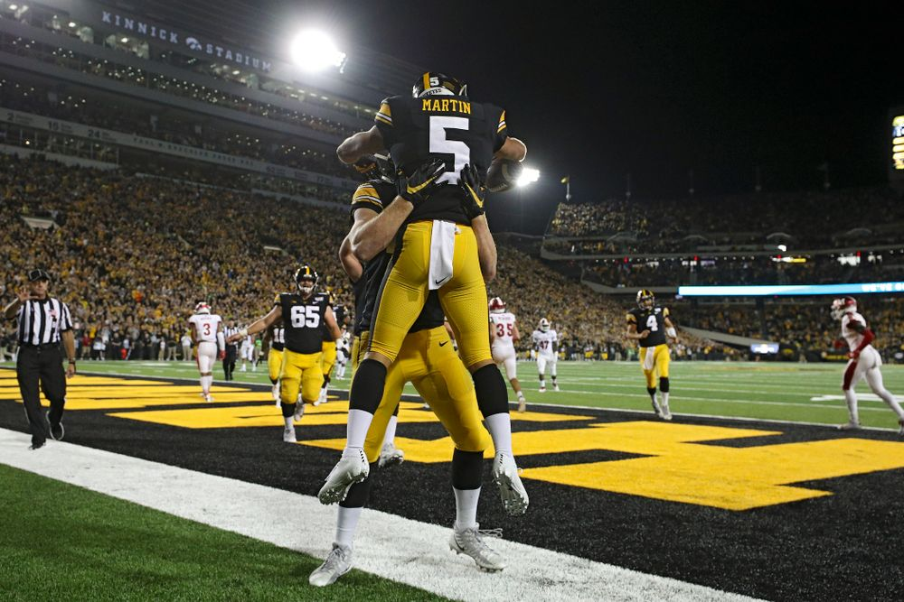 Iowa Hawkeyes tight end Shaun Beyer (42) lfits wide receiver Oliver Martin (5) after he caught a 9-yard touchdown reception during the third quarter of their game at Kinnick Stadium in Iowa City on Saturday, Aug 31, 2019. (Stephen Mally/hawkeyesports.com)