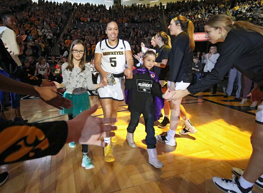 Iowa Hawkeyes guard Alexis Sevillian (5) is introduced with two Go Red for Women Movement Heart Champions before the start of their game at Carver-Hawkeye Arena in Iowa City on Sunday, January 26, 2020. (Stephen Mally/hawkeyesports.com)