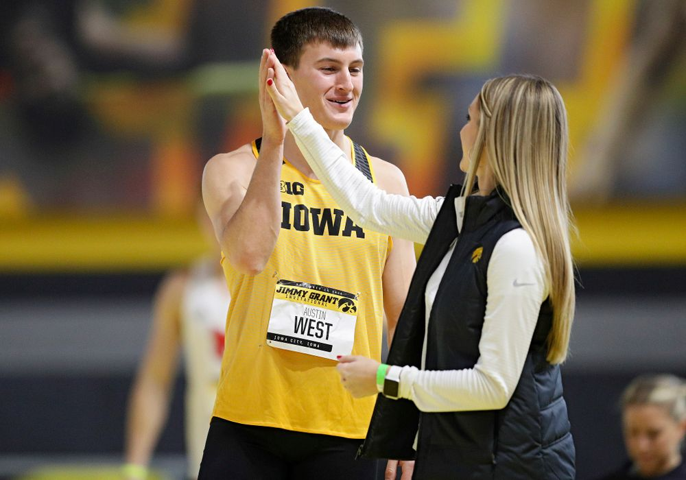 Iowa's Austin West (from left) gets a high-five from assistant coach Paige Knodle as he competes in the men's high jump event during the Jimmy Grant Invitational at the Recreation Building in Iowa City on Saturday, December 14, 2019. (Stephen Mally/hawkeyesports.com)