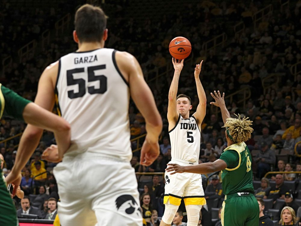 Iowa Hawkeyes guard CJ Fredrick (5) makes a 3-pointer as center Luka Garza (55) looks on during the first half of their game at Carver-Hawkeye Arena in Iowa City on Sunday, Nov 24, 2019. (Stephen Mally/hawkeyesports.com)