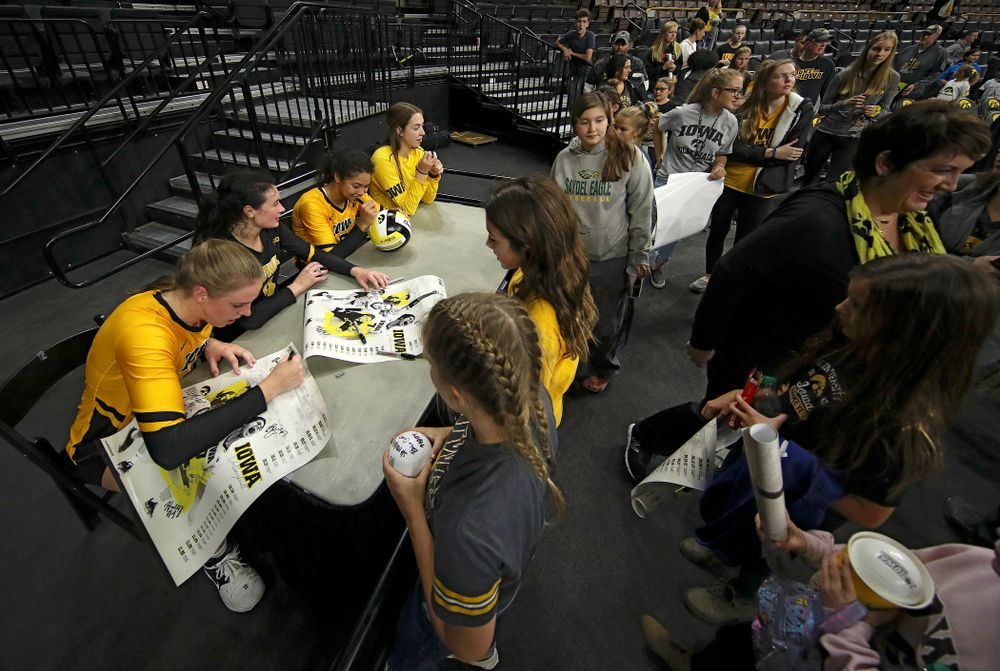 Iowa's Hannah Clayton (18), Halle Johnston (4), Brie Orr (7), and Meghan Buzzerio (5) sign autographs after their match at Carver-Hawkeye Arena in Iowa City on Sunday, Oct 20, 2019. (Stephen Mally/hawkeyesports.com)