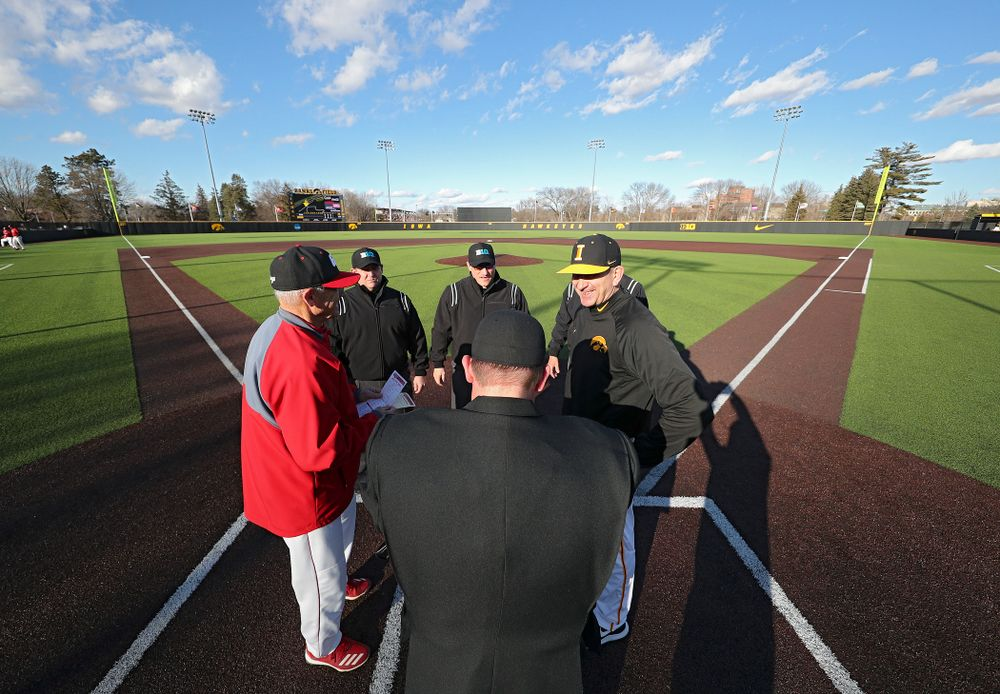 Iowa Hawkeyes head coach Rick Heller meets with the umpires before their game at Duane Banks Field in Iowa City on Tuesday, March 3, 2020. (Stephen Mally/hawkeyesports.com)