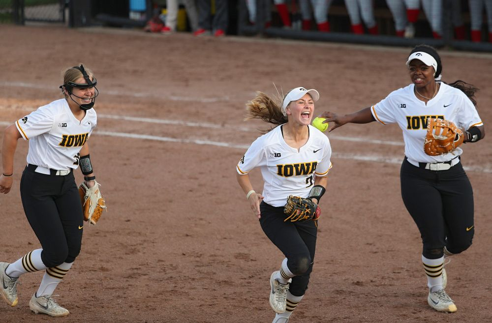 Iowa second baseman Aralee Bogar (center) shouts as she runs back to the dugout with pitcher Sarah Lehman (left) and first baseman DoniRae Mayhew (right) after they turned an inning ending double play during the sixth inning of their game against Ohio State at Pearl Field in Iowa City on Friday, May. 3, 2019. (Stephen Mally/hawkeyesports.com)