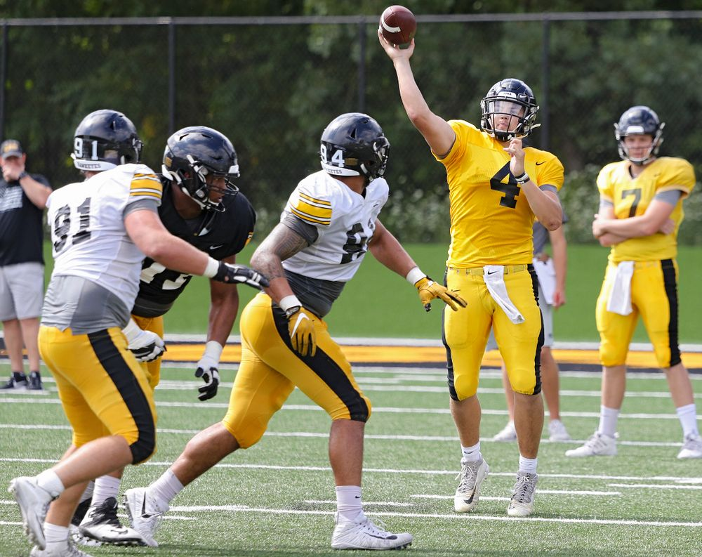 Iowa Hawkeyes quarterback Nate Stanley (4) throws a pass over defensive end A.J. Epenesa (94) during Fall Camp Practice No. 11 at the Hansen Football Performance Center in Iowa City on Wednesday, Aug 14, 2019. (Stephen Mally/hawkeyesports.com)