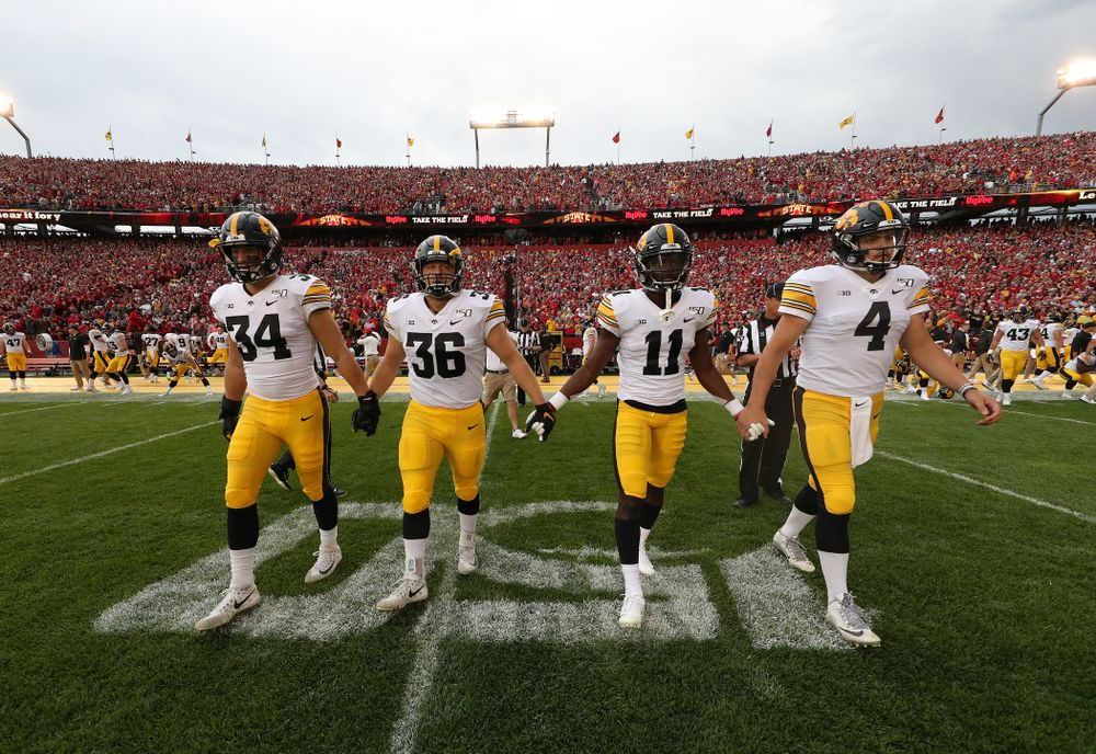 Captains linebacker Kristian Welch (34), fullback Brady Ross (36), defensive back Michael Ojemudia (11), and quarterback Nate Stanley (4) against the Iowa State Cyclones Saturday, September 14, 2019 at Jack Trice Stadium in Ames, Iowa. (Brian Ray/hawkeyesports.com)
