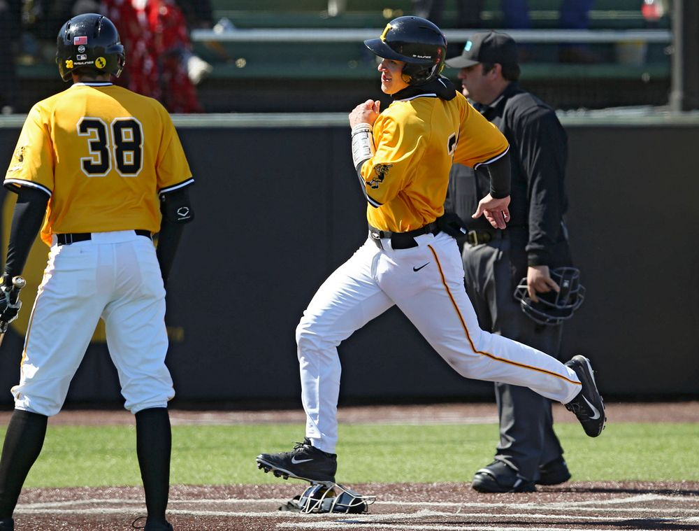 Iowa Hawkeyes catcher Austin Martin (right) scores a run on a wild pitch during Trenton Wallace's (38) at bat during the third inning against Illinois at Duane Banks Field in Iowa City on Sunday, Mar. 31, 2019. (Stephen Mally/hawkeyesports.com)