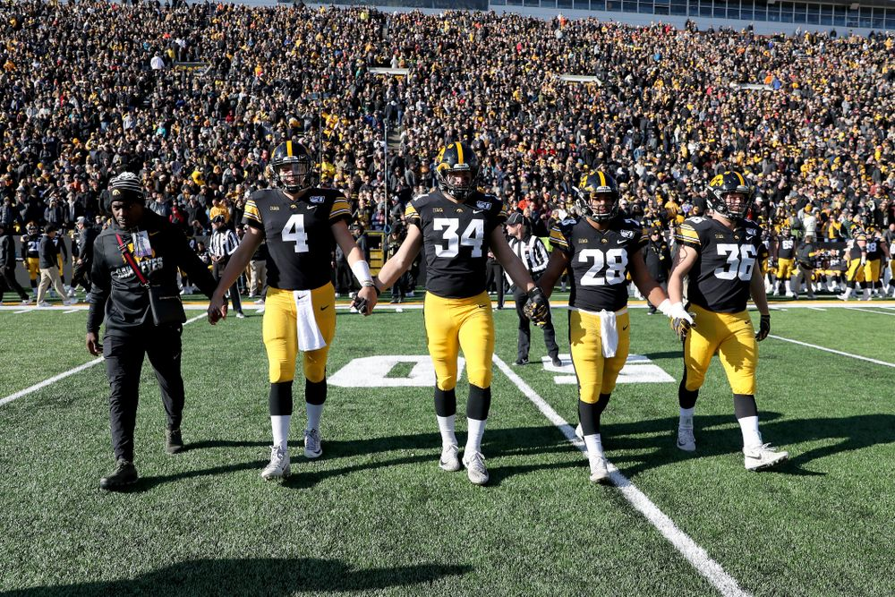 Honorary Captain Desmond King and captains i4o#2], linebacker Kristian Welch (34), running back Toren Young (28), and fullback Brady Ross (36) against the Illinois Fighting Illini Saturday, November 23, 2019 at Kinnick Stadium. (Brian Ray/hawkeyesports.com)
