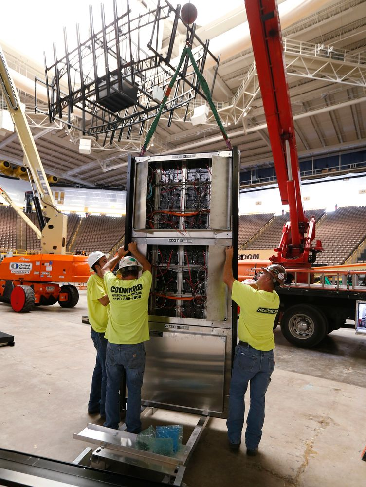Workers install the video board at the south end of Carver.