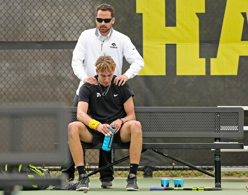 Iowa head coach Ross Wilson (top) talks with Nikita Snezhko during a match against Ohio State at the Hawkeye Tennis and Recreation Complex in Iowa City on Sunday, Apr. 7, 2019. (Stephen Mally/hawkeyesports.com)