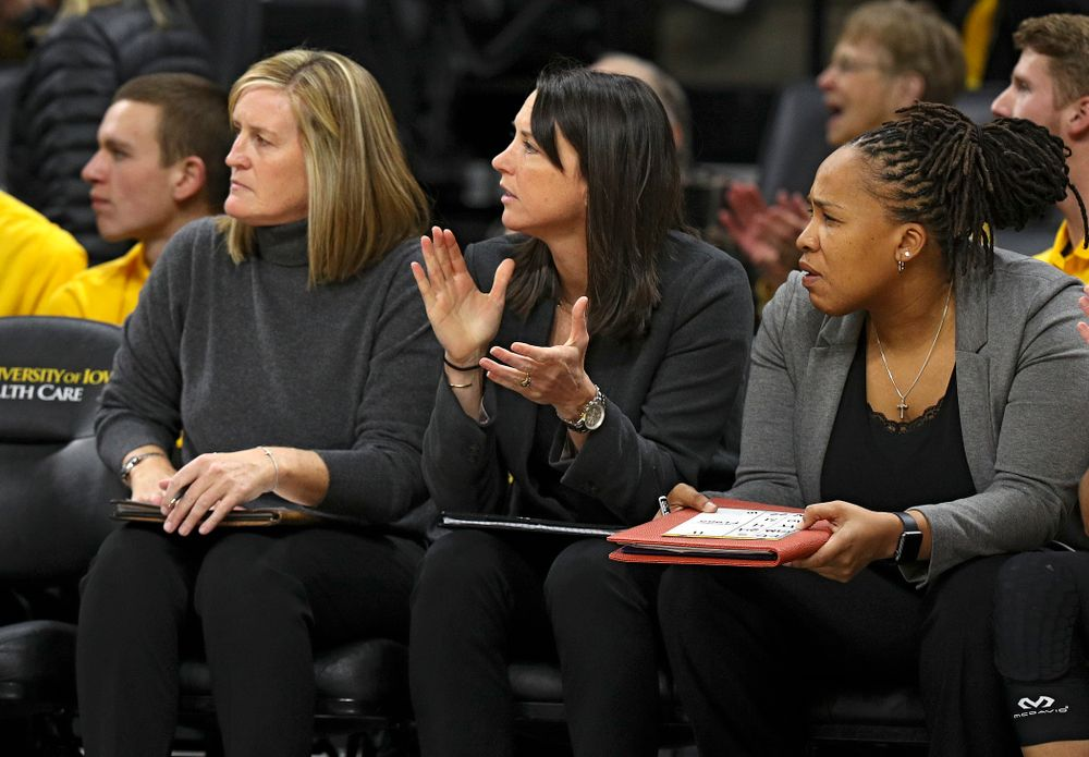 Iowa assistant coach Abby Stamp (center) claps between special assistant to the head coach Jenni Fitzgerald (left) and assistant coach Raina Harmon (right) during the third quarter of their overtime win against Princeton at Carver-Hawkeye Arena in Iowa City on Wednesday, Nov 20, 2019. (Stephen Mally/hawkeyesports.com)