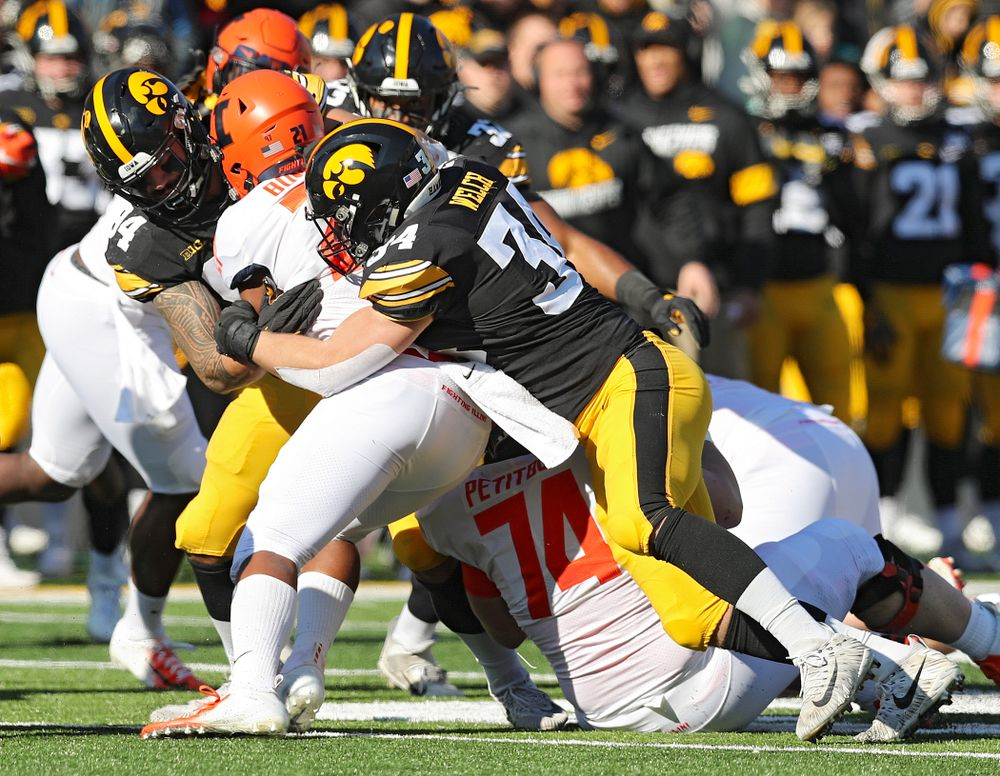Iowa Hawkeyes defensive end A.J. Epenesa (94) and linebacker Kristian Welch (34) make a tackle during the first quarter of their game at Kinnick Stadium in Iowa City on Saturday, Nov 23, 2019. (Stephen Mally/hawkeyesports.com)